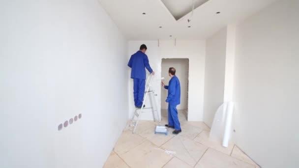 Pracovní aplikovat lepidlo na zdi vedle pracovníků, stojící na žebříku