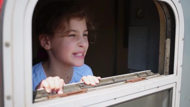 Malá holčička vypadá z okna