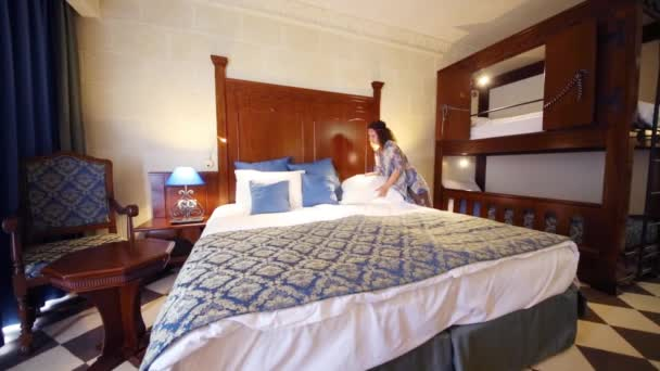 Frau legt sich auf Doppelbett