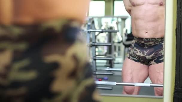 Kulturista se dívá na své svaly v zrcadle v tělocvičně hala