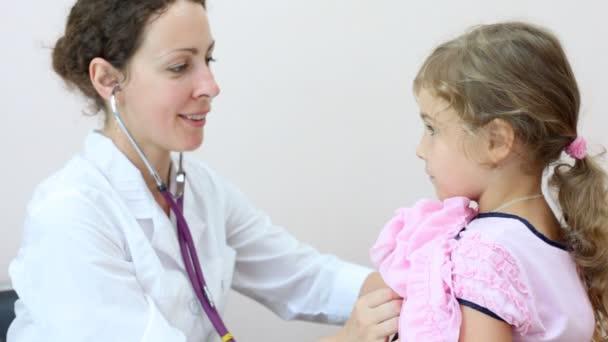 Žena lékař poslouchá holčička