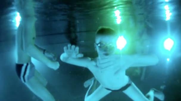 Chlapec plave pod vodou v bazénu