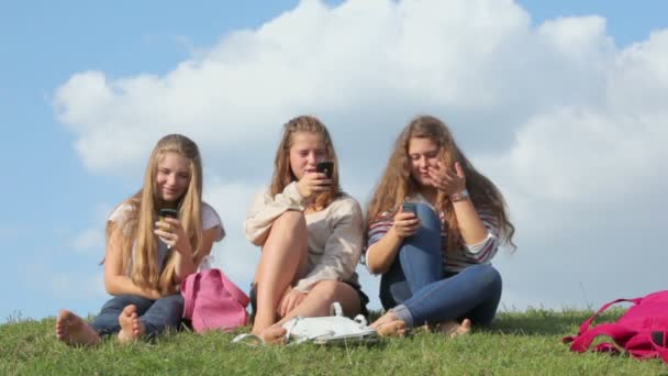 Three girls use cell phones
