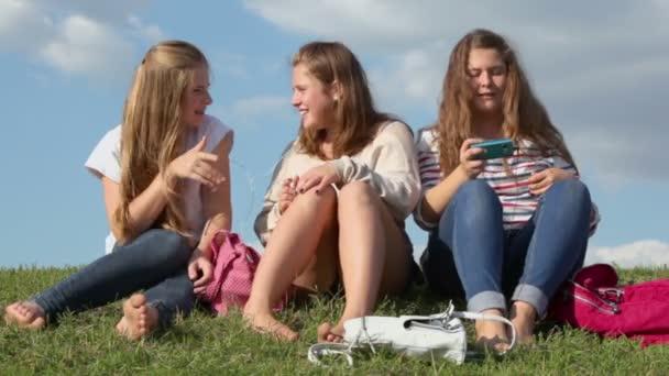 Three girls listen music and sing