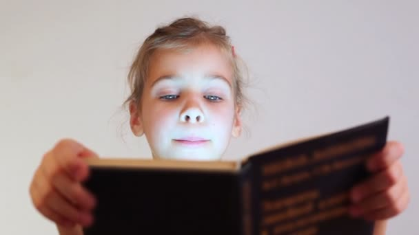 Little girl reads book attentively