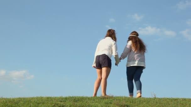 Dvě dívky drží za ruce