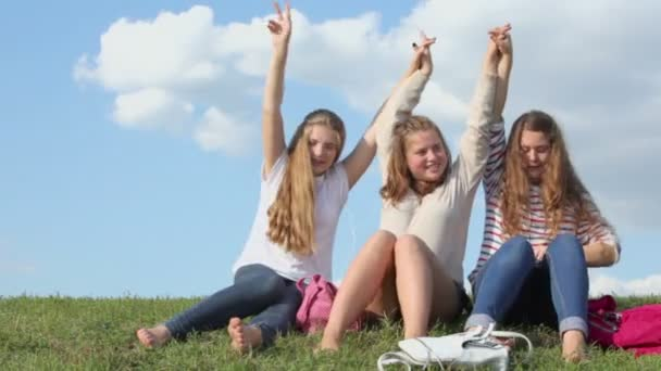 Three girls sways with hands up