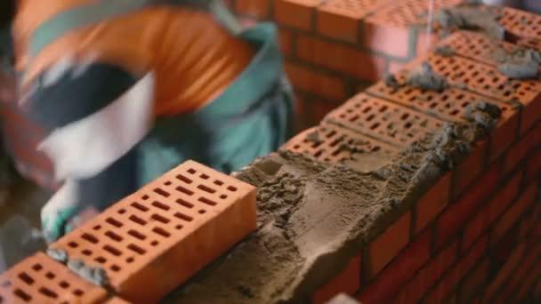 Dělník staví cihlová zeď s lopatkou