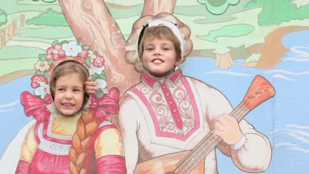 zwei Kinder im Rahmen mit gemalten Menschen