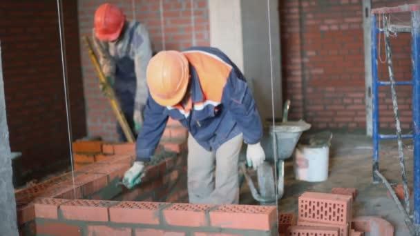Několik pracovníků budovat cihlová zeď