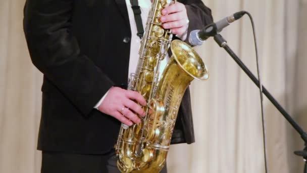 Férfi öltöny szaxofonon játszik