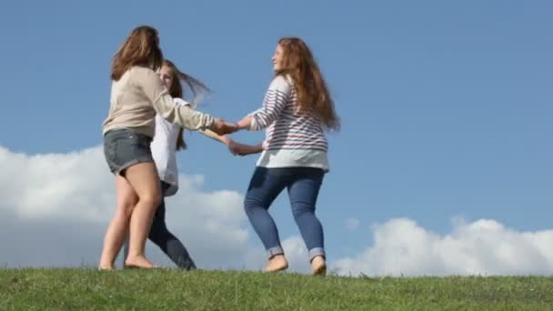 Three girls hold hands and circling