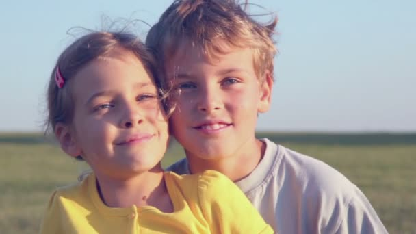 Two kids sit on grass hill