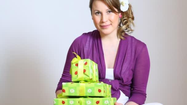Těhotná žena držící 3 giftboxes