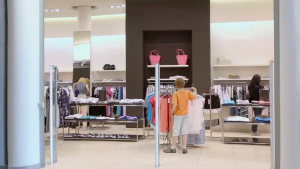 Malý chlapec vejde v obchodě s oděvy dámské