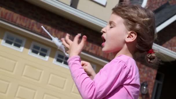 Little girl eats candy floss
