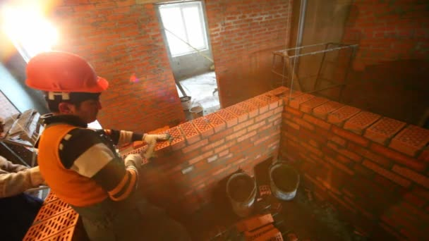 Dva pracovníci stavět zeď v pokoji