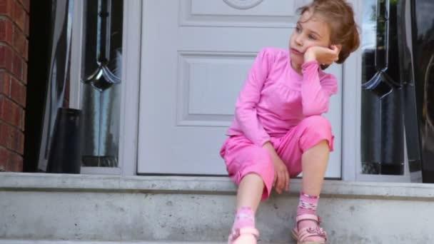 Malá holka sedí na verandě