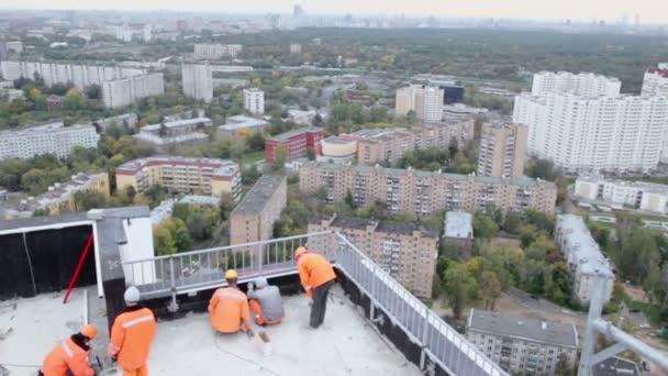 Arbeiter errichten Zaun auf Dach