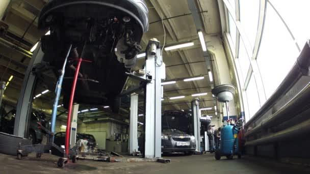 Car mechanics elevate car on lifting-jack hoist in garage