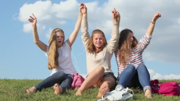 Three girls hold raised hands