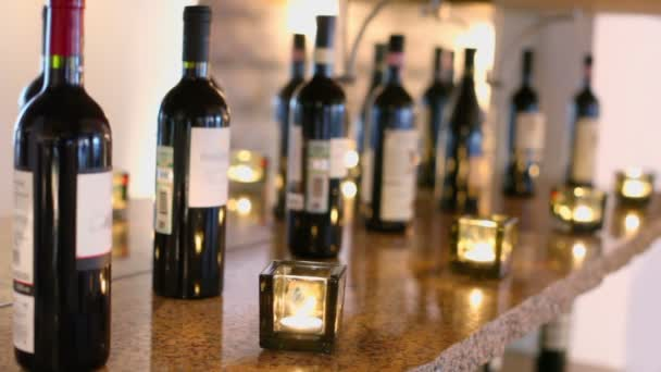 Bottles of wine and candles burn in restaurant