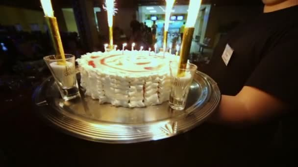 Waiter carries birthday cake with candles