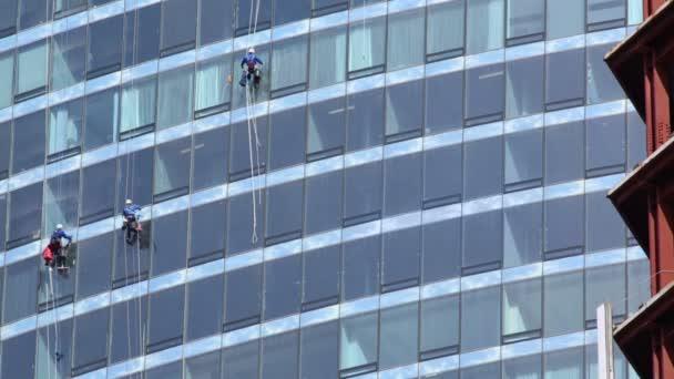 Tři zaměstnanci umýt okna mrakodrapu