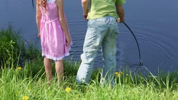 Zwei Kinder sitzen in Teichnähe