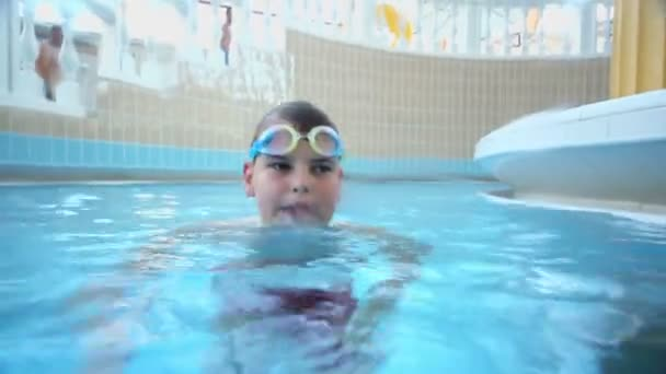 Young boy swims at pool