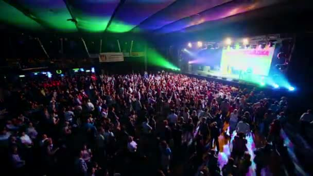 Crowd of people stand near stage