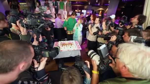 Stars und Kameraleute bei Präsentation nahe am Kuchen