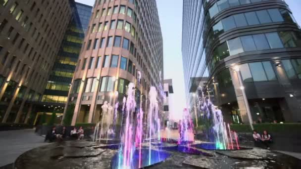 Fountain with people near office buildings