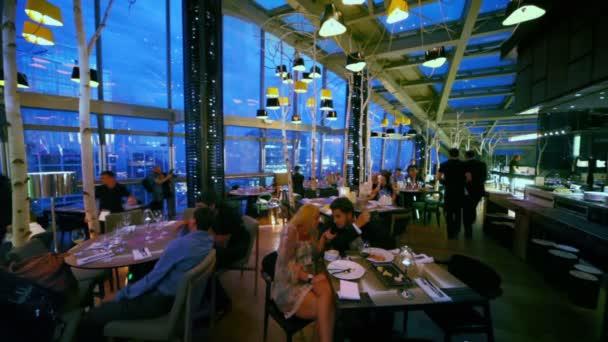 Lidé sedí v restauraci šedesát