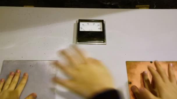 Kinder legen Hände an Elektrodenplatten.