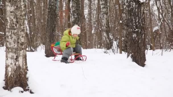 Nettes kleines Mädchen beim Rodeln im Winter