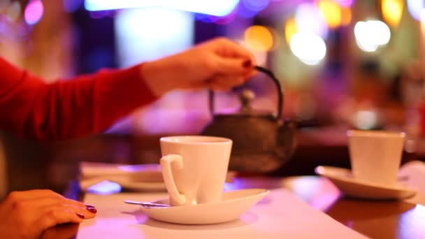 Woman pouring tea from teapot