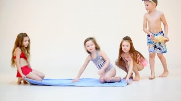 Čtyři děti sedící na plážový ručník