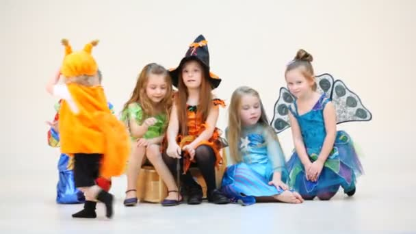 Six children in costumes siting