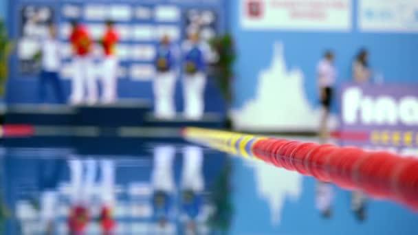Sportolók állni a talapzat medence közelében