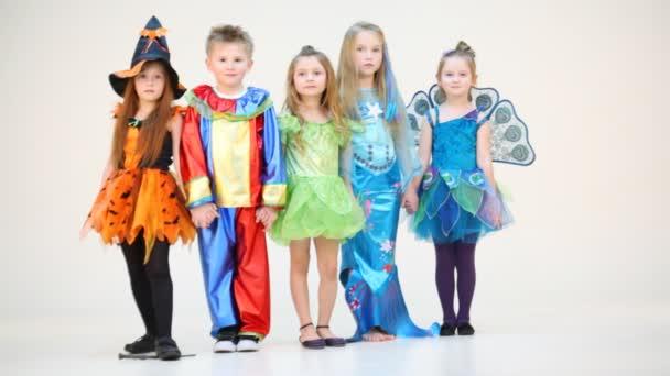Five children in costumes holding hands