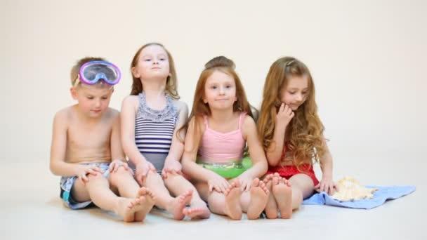 vier Kinder sitzen auf einem Badetuch