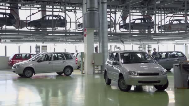 Lidé pracují na dopravník s nové automobily