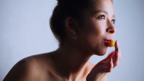 Atraktivní mladá model kouše ovoce