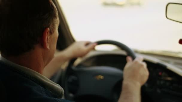 Man turns steering wheel of car