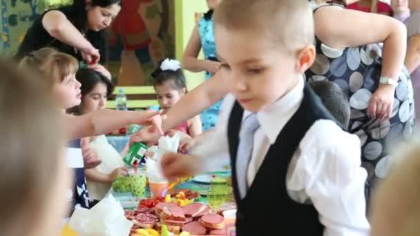 Kinder essen beim Fest im Kindergarten