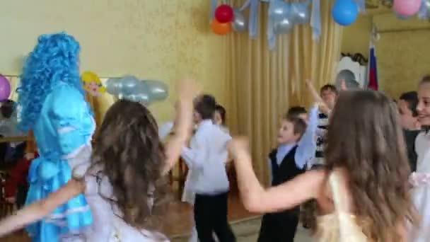 Děti tančí s tváří jako Pinocchio a Malvína