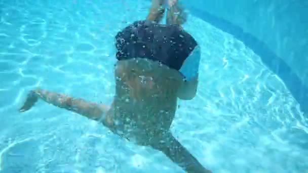 Teen boy under water in pool
