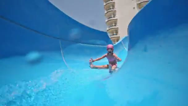 Girl rolls on blue waterslide