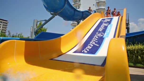 Girls and boy ride on water slide